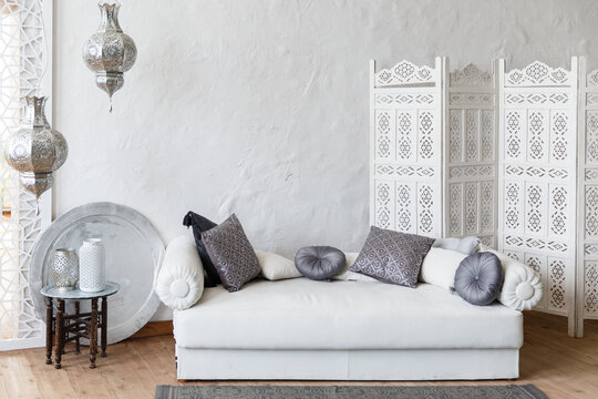 Eastern traditional interior. Morocco style room. Arch and window with beautiful carving. White and gray room with beautiful white sofa and pillows