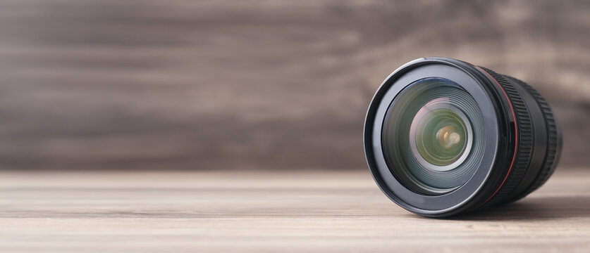 Camera lens on the wooden table.