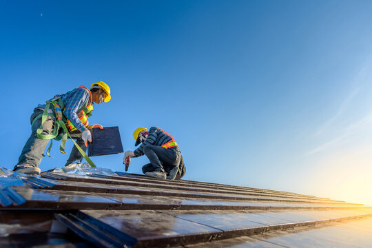 Two male workers wearing safety clothes Installing the roof tile house That is a ceramic tile roof On the construction site