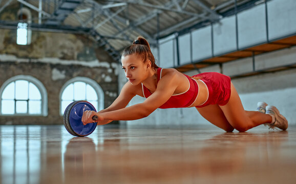 Beautiful strong woman in sportswear trains with exercise wheel in the gym or club. Sports and recreation concept.
