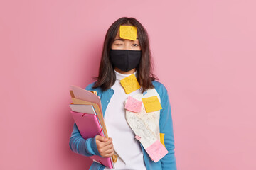 Prevention of virus spread. Serious brunette woman wears black disposable face mask busy doing...