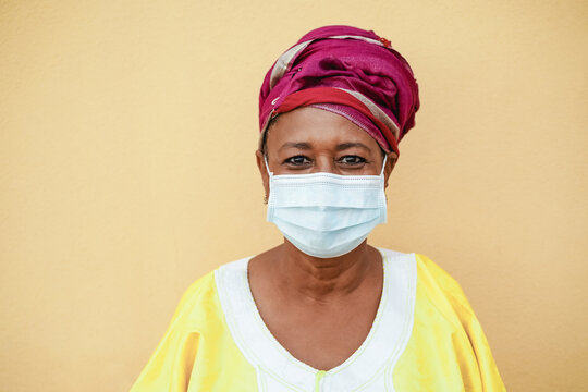 Happy senior black woman with face mask wearing traditional african dress during coronavirus outbreak  - Focus on face