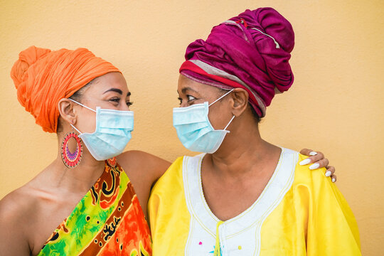 Happy mother and daughter wearing traditional african dresses during coronavirus outbreak - African people with face safety mask having fun - Social distance concept - Focus on faces