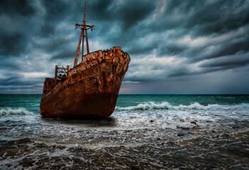 A stranded shipwreck at surf with rough sea and stormy sky