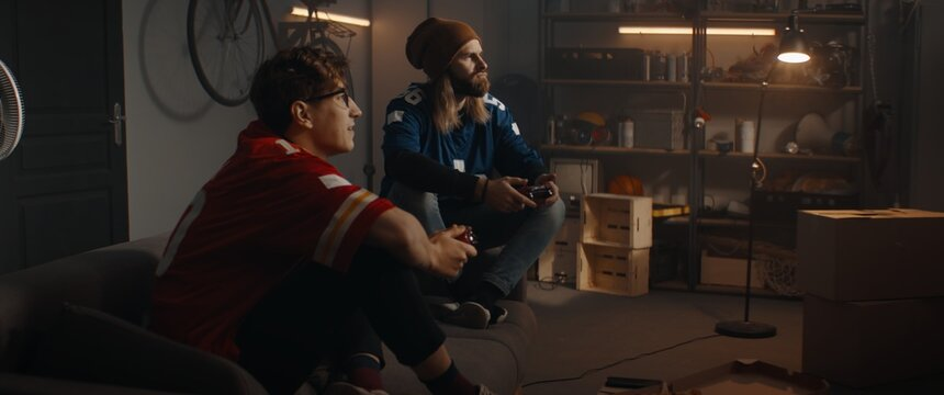 Two friends hanging out, sitting on sofa, playing video game inside garage