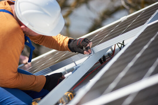 Male workers installing stand-alone solar photovoltaic panel system. Electricians mounting blue solar module on roof of modern house. Alternative energy environmental ecology concept.