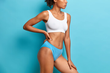 Unrecognizable dark skinned woman in cropped top and panties has slim figure flat belly...