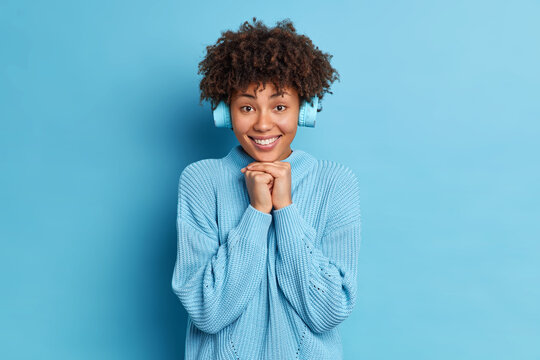 Pretty African American woman keeps hands under chin smiles pleasantly listens audio track via stereo headphones dressed in knitted jumper isolated over blue background. People and lifestyle concept
