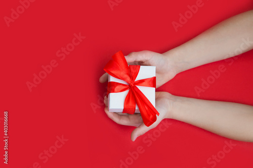 Children's hands hold gift box on a red background. A concept by the Mother's Day.  Father's day. Birthday.