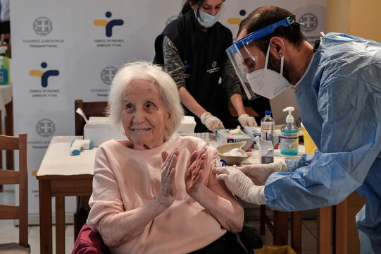 An elderly woman claps her hands after receiving a vaccine against the coronavirus disease (COVID-19) at a nursing home in Athens