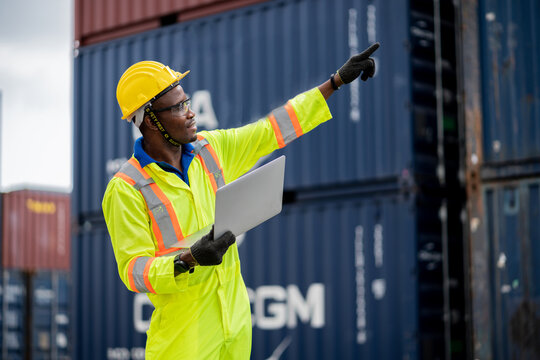 engineer man / worker in safety jumpsuit uniform with yellow hardhat and use laptop computer control at cargo container ship port warehouse.transport import,export logistic industrial service