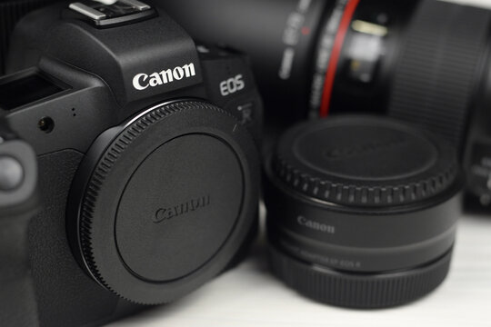 Canon EOS R photocamera and mount adapter EF - EOS R with Canon 105mm f2.8 and Sigma 24-105 f4 Art lenses on white wooden table