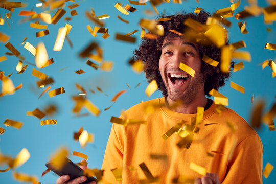 Celebrating Young Man With Mobile Phone Winning Prize And Showered With Gold Confetti In Studio