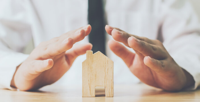 Insurance house and save money for property investment real estate concept. Man hands prevent wooden home