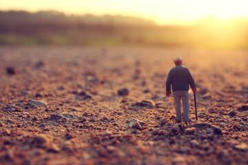 Surreal image of mysterious man walking alone in field during sunset