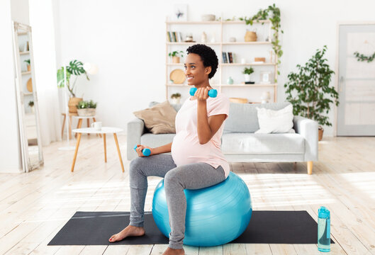 Pregnant black woman sitting on fitness ball, working out with dumbbells in her home gym