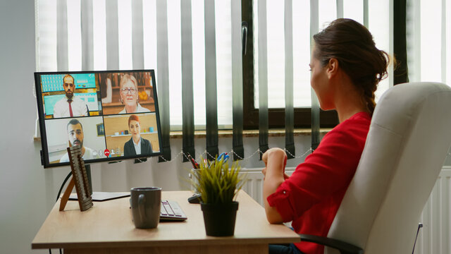 Woman talking with colleagues about project on video call. Freelancer working with business remotely team discussing chatting having virtual online conference meeting webinar using internet technology