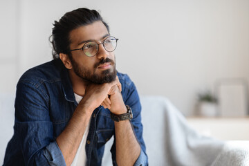 Portrait Of Thoughtful Millennial Arab Guy In Glasses Resting Head On Hands