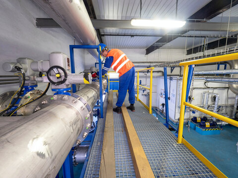 Worker checks the valves behind the compressors of the high-pressure biogas circuit