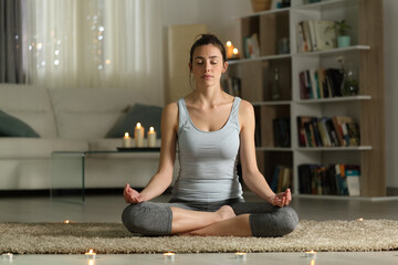 Woman doing yoga exercise in the night at home with candles