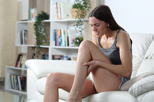 Woman suffering a cramp in the calf muscle at home