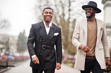 Two fashion black men walking on street. Fashionable portrait of african american male models. Wear...