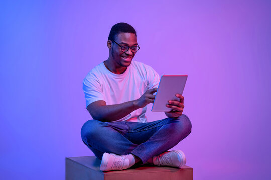 Young black freelancer guy sitting with digital tablet under luminous neon light