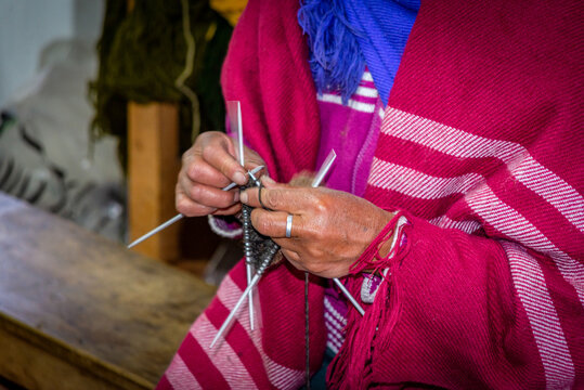 An elderly native woman's hands sewing and working on wool clothing