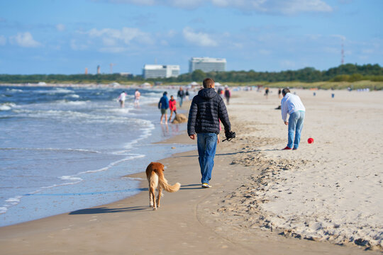 Urlauber beim Spaziergang am Strand von Swinemünde an der polnischen Ostseeküste