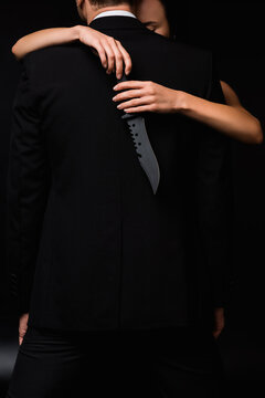 partial view of dangerous woman holding knife behind back of man isolated on black