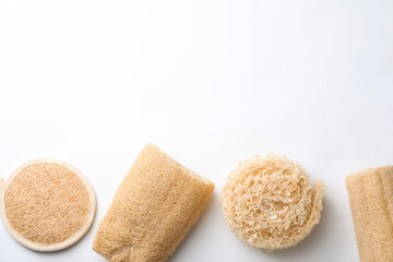 Wall Mural - Natural shower loofah sponges on white background, top view