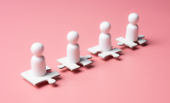 People figures on puzzles on pink background,human resources and management concept