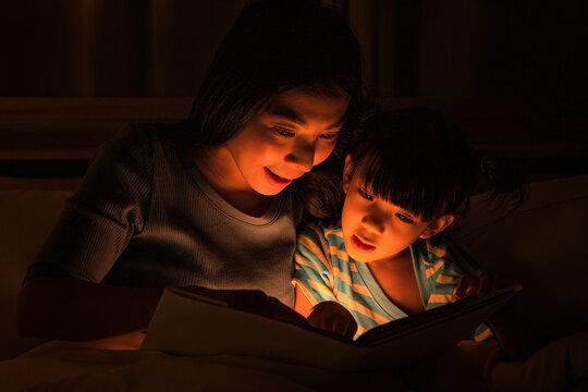 mom and daughter have goodtime reading bedtime stories for daughter