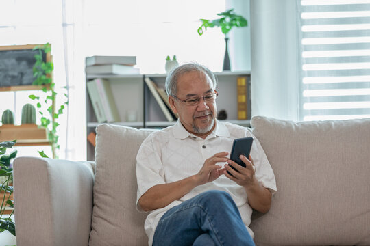 Happiness elderly asian man sitting on sofa using mobile phone and social media smile at home,Senior lifestyle at home concept