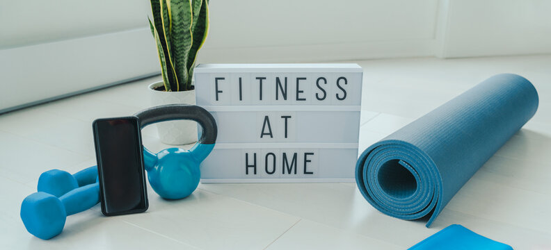 Fitness at home lightbox sign in living room for online workout on phone app training indoors with dumbbell weights and resistance bands on yoga mat banner background.