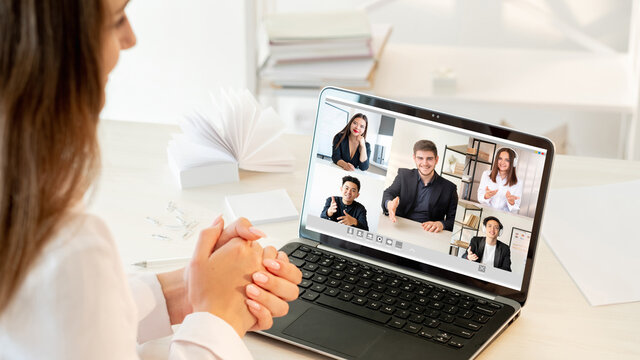 Video call. Virtual meeting. Online teamwork. Pandemic WFH. Ambitious diverse multiracial team greeting new employee on laptop screen at light modern home office.