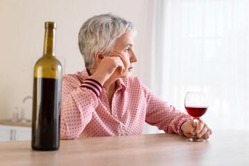 Obraz Stressed senior woman drinking wine at home - fototapety do salonu