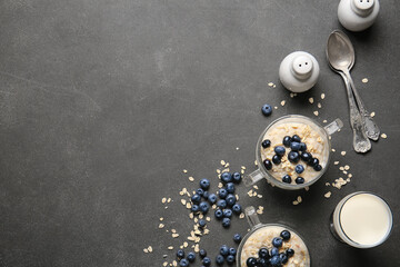 Bowls with tasty oatmeal and blueberry on dark table