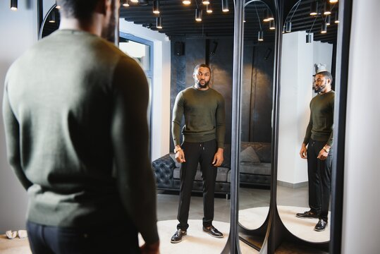 Stylish casual african american man at fitting room clothes store, looking on mirror. The concept of stylish men's clothing.