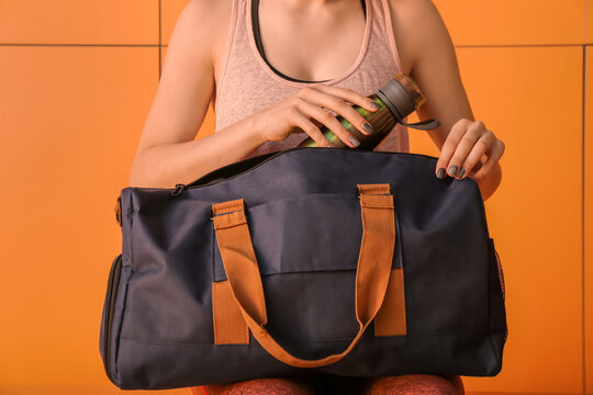 Woman with sport bag in gym locker room