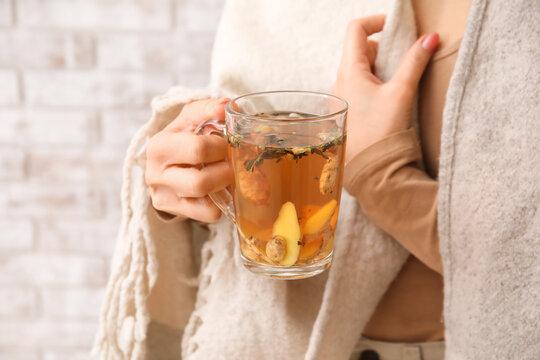 Woman holding cup of hot ginger tea, closeup