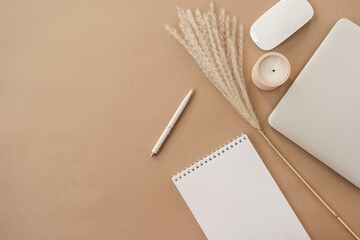 Flatlay of spiral flip notebook with blank paper sheet. Laptop, pampas grass, stationery on beige...