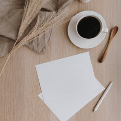 Blank paper sheet on beige wooden table. Artist home office desk workspace with washed linen...