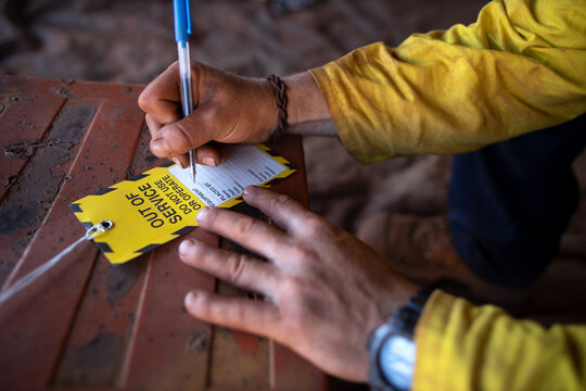 Safe workplaces practices construction worker wearing long sleeve shirt using a blue pen writing on yellow out of service tag prior tagging on damaged faulty goods equipment