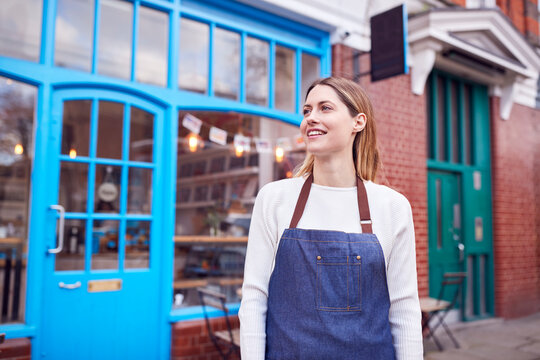 Portrait Of Smiling Female Small Business Owner Standing Outside Shop On Local High Street