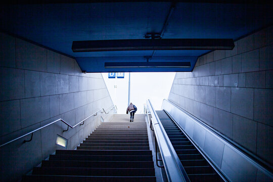 a person in a beige jacket walking up the stairs at a trainstation in munich