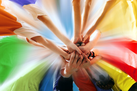 Sports Team All Hands Together. Happy Teammates Standing Together in Circle With All Hands  on Deck. Teamwork in Sports Team. Group of Young Players in Colourful Shirts Showing Team Power