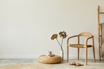Neutral concept of living room interior with design wooden chair, round carpet, dried flowers in...