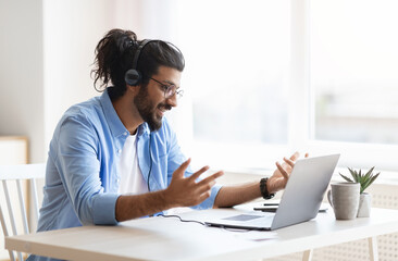 Web Conference. Arabic Freelancer Guy In Headset Making Video Call On Laptop