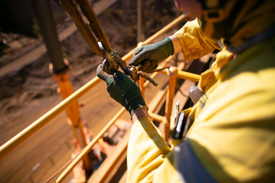 Safe work practices top view of rigger crane high risk worker wearing a safety glove fastening pin into D- shackle 4.5 ton lifting lug together with lift sling safety tagline prior load being lifted